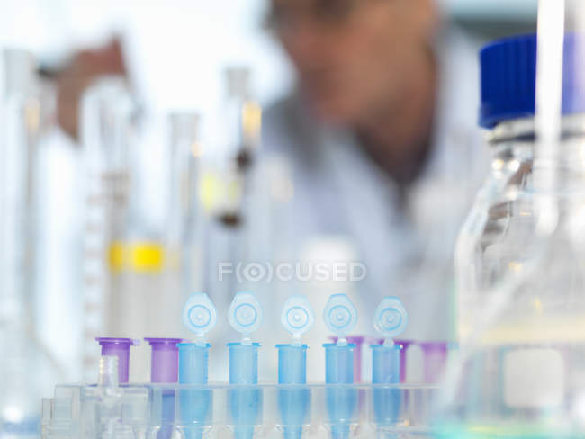 Row of eppendorf vial awaiting sample for testing in laboratory, scientist out of focus in background — Stock Photo