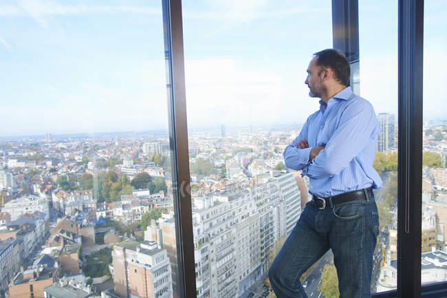 Businessman looking from office window at Brussels cityscape, Belgium — Stock Photo