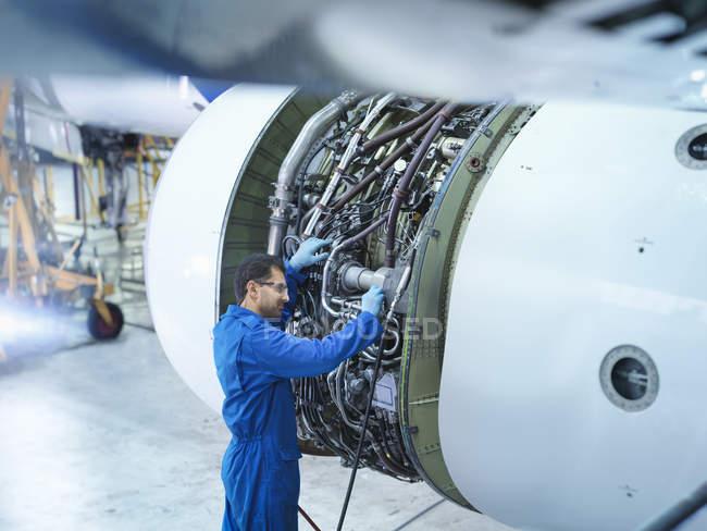 Инженеры работают над реактивным двигателем на авиаремонтном заводе — стоковое фото