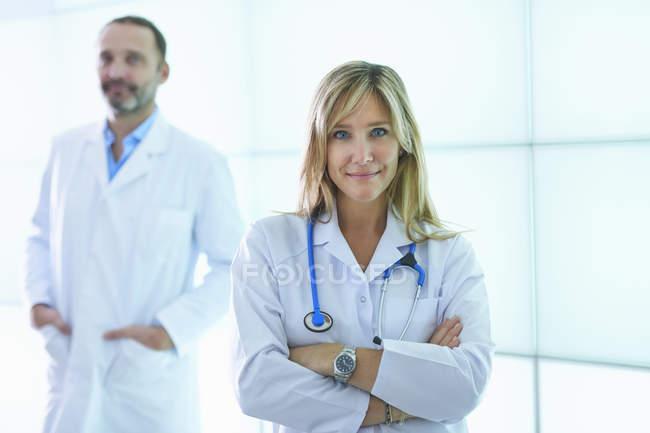 Médicos posando contra painel de parede retroiluminado — Fotografia de Stock
