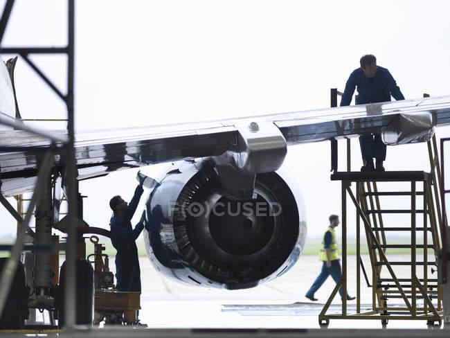 Инженеры, работающие на крыло самолета в поддержание авиазавод — стоковое фото