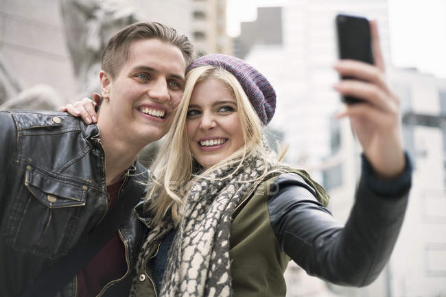 Young Couple Posing For Smartphone Selfie On Street New York USA Stock Photo