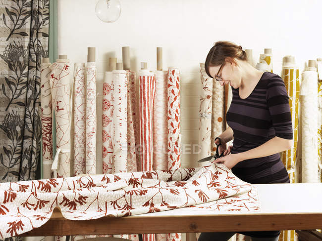 Woman cutting fabric on work table in hand-printed textile workshop — Stock Photo