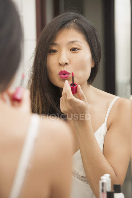 Mid adult woman applying lip gloss — Stock Photo