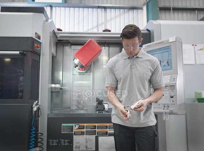 Ingénieur avec tour CNC faisant des articulations de hanche artificielles dans l'usine orthopédique — Photo de stock