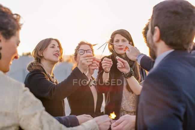 Gruppe von Freunden Beleuchtung funkelt bei Party auf dem Dach — Stockfoto