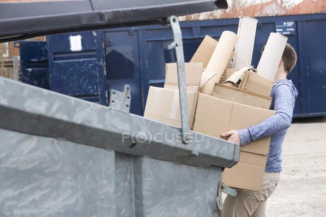 Adolescent transportant des déchets de carton à la poubelle de recyclage — Photo de stock