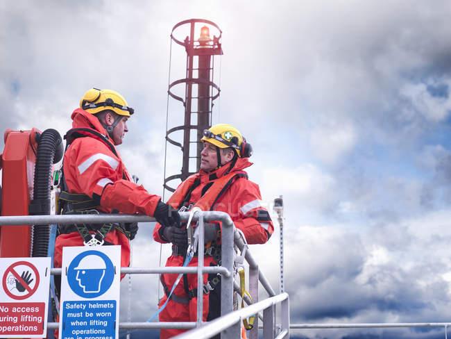 Travailleurs de parc éolien offshore dans la discussion sur la jetée en mer — Photo de stock
