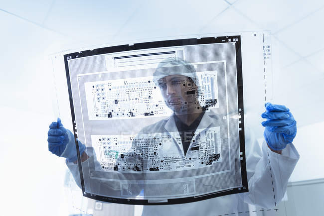 Worker inspecting circuit board negative sheet in circuit board factory — Stock Photo