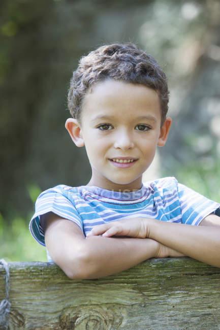 Портрет мальчика, опирающегося на садовый забор — стоковое фото