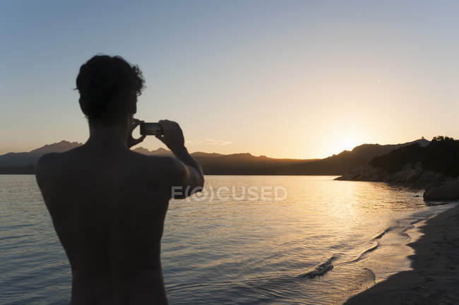 Man taking photograph of sunset over sea — Stock Photo