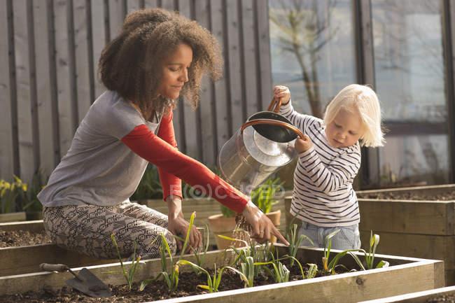 Mitte Erwachsene Frau hilft Sohn Wasserpflanzen im Hochbeet — Stockfoto