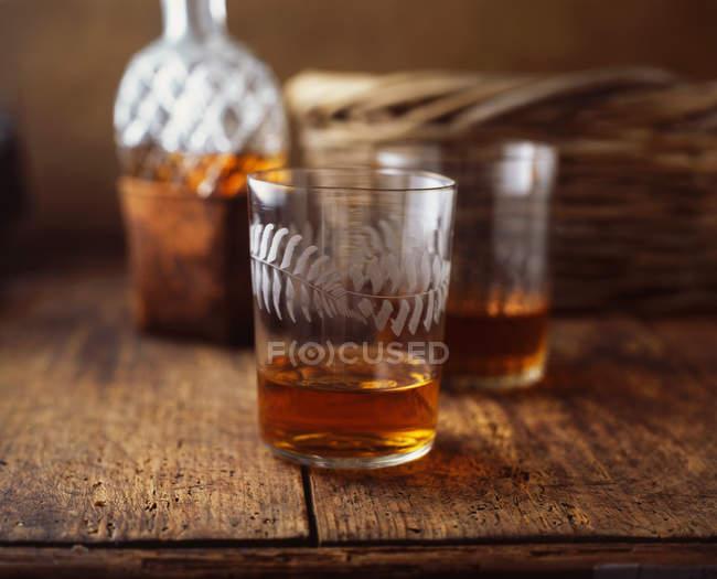 Gläser und eine Flasche Whisky auf Holztisch — Stockfoto
