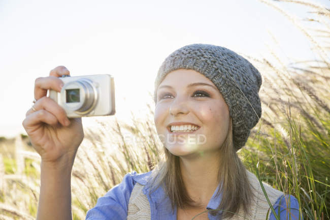 Young woman taking photograph with camera in field — Stock Photo