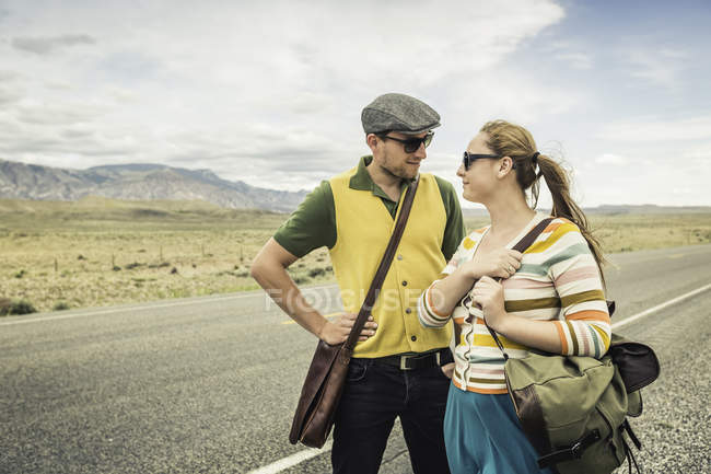 Retro style couple looking at each other on roadside, Cody, Wyoming, USA — Stock Photo