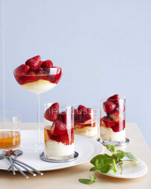 Drinking glasses filled with champagne strawberry desserts — Stock Photo
