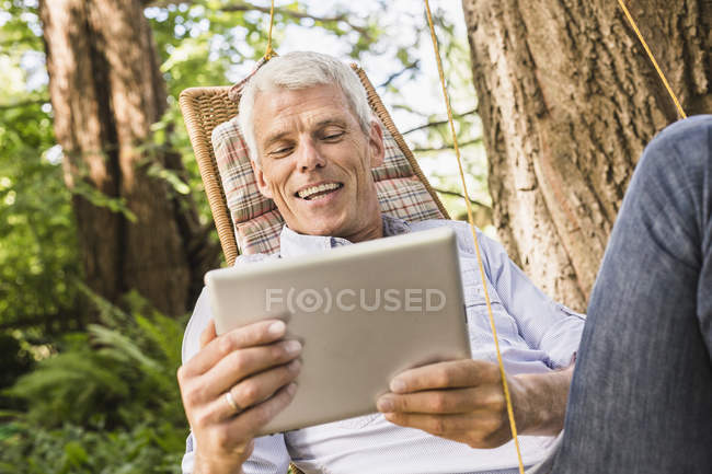 Mature man using digital tablet on hammock — Stockfoto