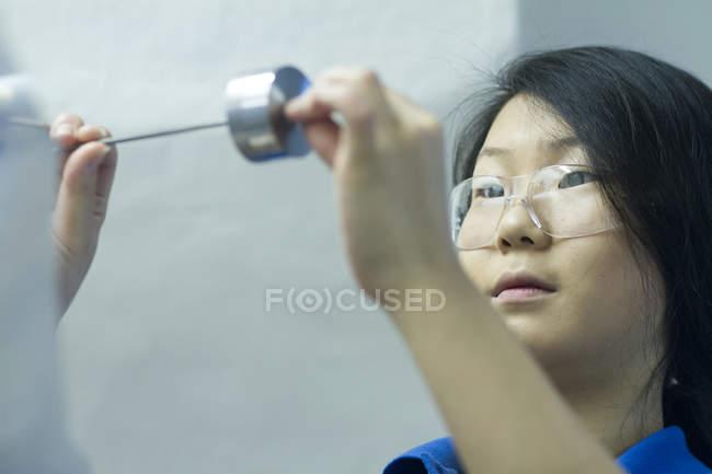 Молодая женщина в защитных очках с металлическим компонентом — стоковое фото