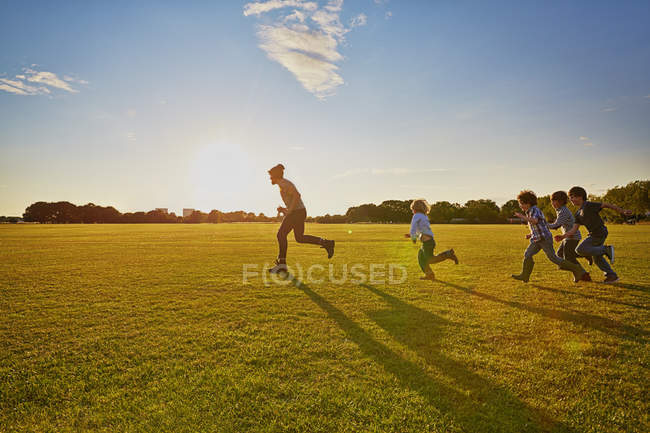 Family enjoying outdoor running in park — Stock Photo
