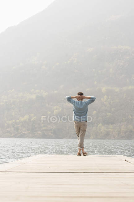 Rear view of young man looking out from pier, Lake Mergozzo, Verbania, Piemonte, Italy — Stock Photo