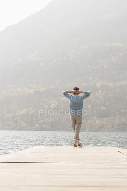 Veduta posteriore del giovane che guarda fuori dal molo, Lago Mergozzo, Verbania, Piemonte, Italia — Foto stock