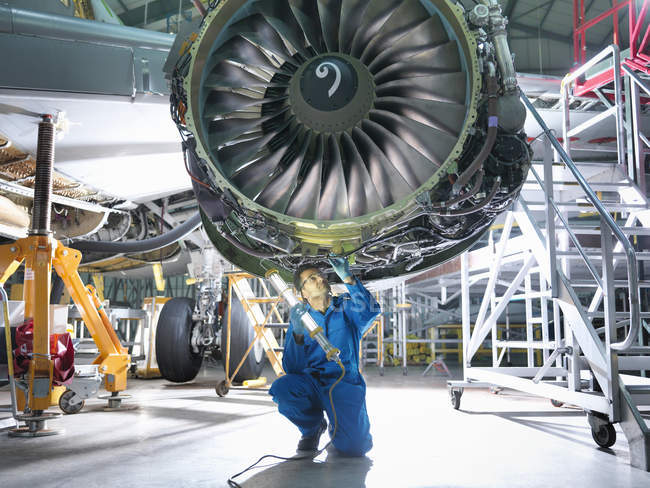 Engineer inspecting jet engine in aircraft maintenance factory — Stock Photo