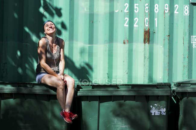Femme heureuse assise sur la corbeille à côté du conteneur vert — Photo de stock