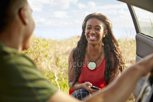 Молода жінка на проведення смартфон посміхаючись двері відкриті автомобіля — стокове фото