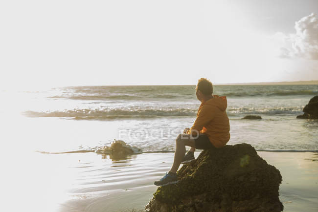 Mature man, sitting on rock, looking out to sea — Stock Photo