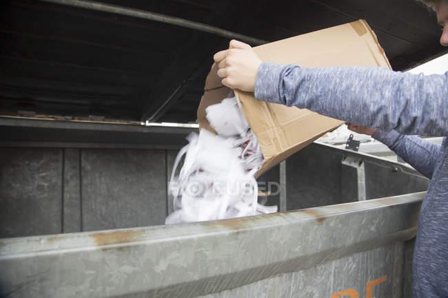 Adolescent vider les déchets de papier à la poubelle de recyclage — Photo de stock