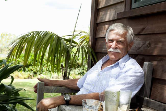 Senior uomo relax in cabina di legno, Raglan, Nuova Zelanda — Foto stock