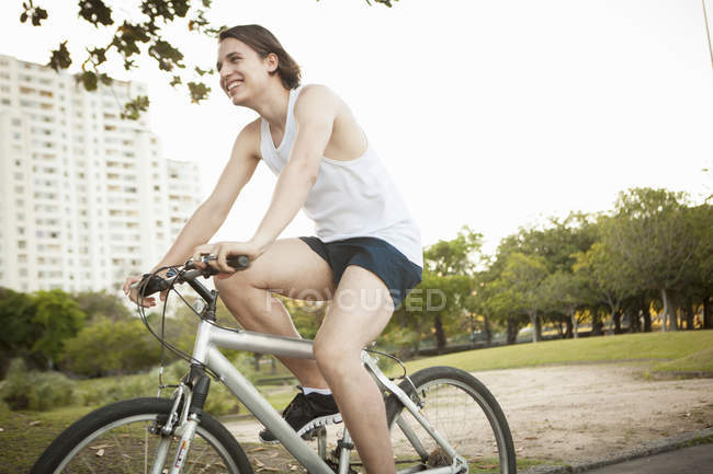 Young man cycling in park — Stock Photo