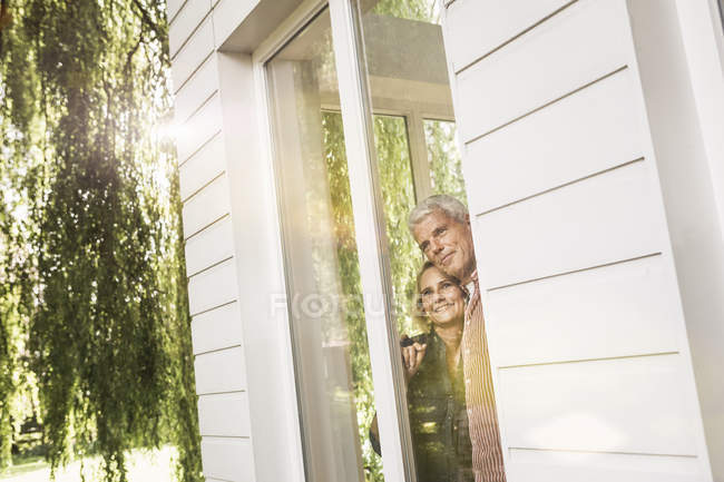 Husband and wife looking out of window into garden — Stockfoto