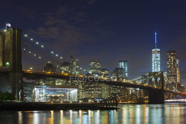 Vista nocturna del distrito financiero de Manhattan y puente de Brooklyn, Nueva York, Estados Unidos - foto de stock