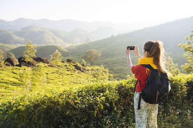Junge Frau fotografiert Teeplantagen in der Nähe von Munnar, Kerala, Indien — Stockfoto