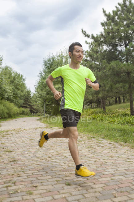 Young male runner running in park — Stock Photo