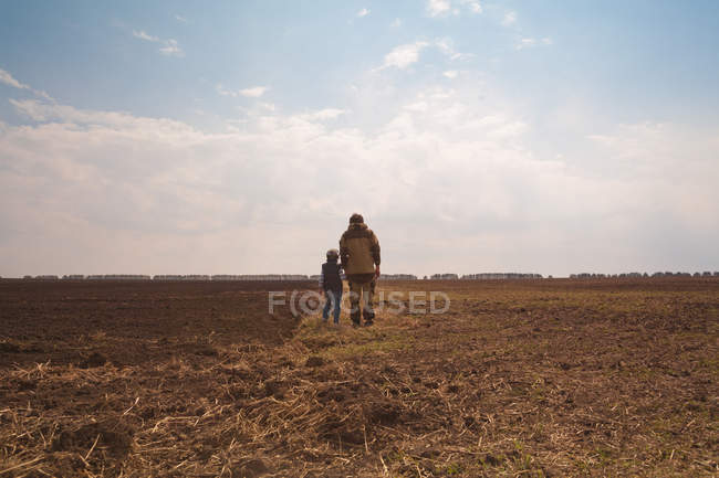 Отец и сын стоят вместе в поле, вид сзади — стоковое фото