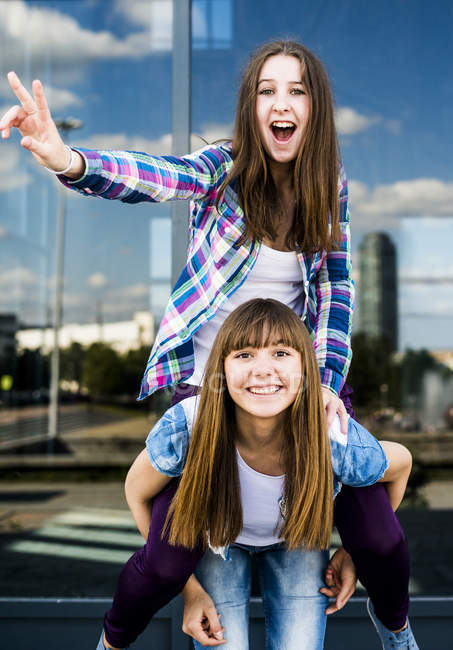 Two young women making peace sign and piggybacking — Stock Photo