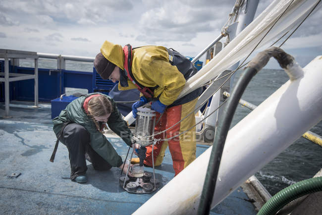 Marine biologist taking plankton samples from net on research ship — Stock Photo