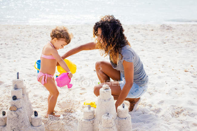 Mother and toddler daughter building sandcastle on beach, Tuscany, Italy — Stock Photo