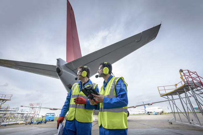 Airside engineers inspecting jet aircraft on runway — Stock Photo