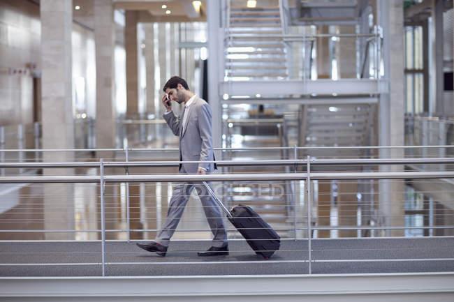 Молодой бизнесмен с колесным случаем на дорожке конференц-центра — стоковое фото