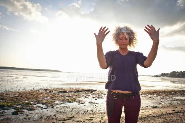 Femme mature faisant de l'exercice sur la plage — Photo de stock