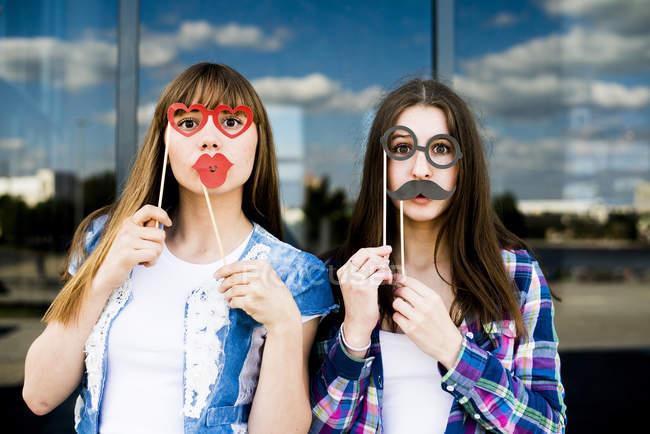 Portrait of two young women holding up lips and glasses costume masks — Stock Photo