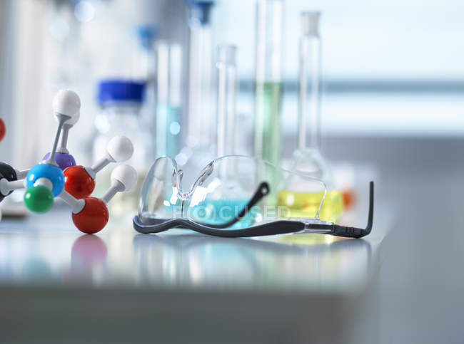 Safety glasses and molecular model on laboratory bench, scientific equipment in background — Stock Photo