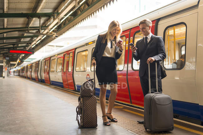 Empresario y mujer de negocios mensajes de texto en la plataforma, Estación de metro, Londres, Reino Unido - foto de stock