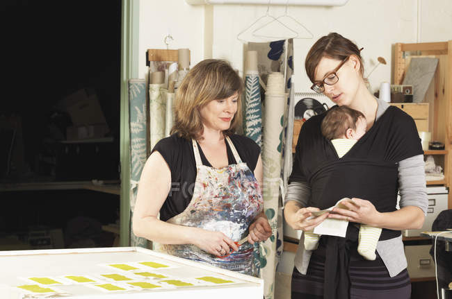Women discussing design in hand-printing textile workshop — Stock Photo