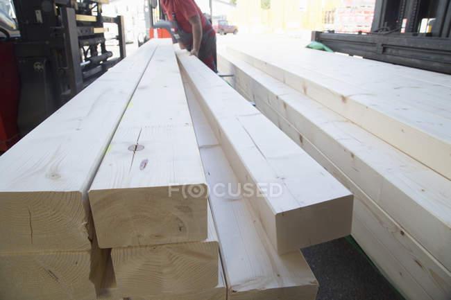 Lagerarbeiter stapelt Holzbohlen für Baumarkt — Stockfoto