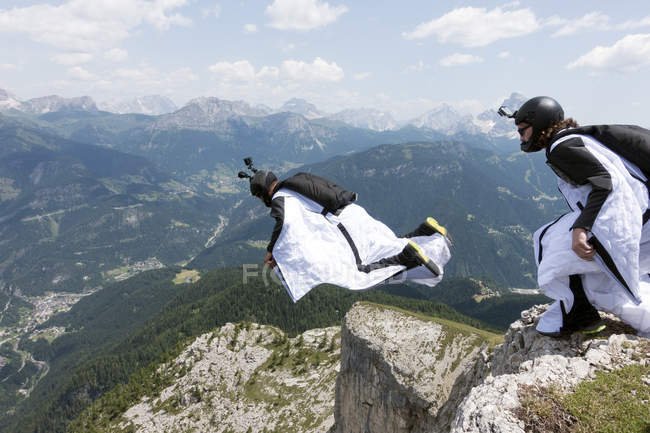 Two male BASE jumpers exiting from mountain top, Dolomites, Italy — Stock Photo