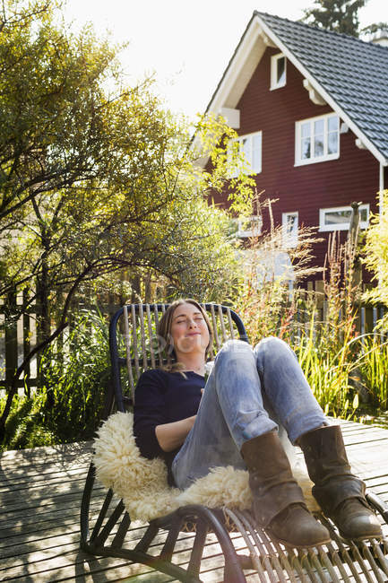 Mujer adulta media relajante en silla de salón en cubierta de madera - foto de stock